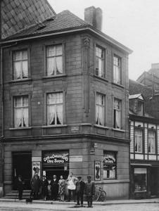 Les propriétaires (Marie 3e et Jonas 4e) semblent avoir vieilli. Sur le côté, rue du Marché, on voit la 2e petite maison où Edouard Fléron faisait commerce de tabac, cigares avec sa femme.
