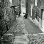 1960 :  M. Collinet bavarde avec une petite fille dans une rue qui a subi beaucoup de travaux : des pavés ont été remplacés par de l'asphalte, l'avaloir n'a pas été reconstitué et les pavés anciens sont mal assemblés.