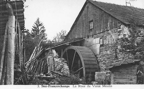 Carte postale: 1930: le meunier pose à côté de la roue de l'ancien moulin banal
