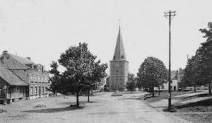 1920: la place du Marché (carte postale) De gauche à droite: la laiterie «La Concorde»,  la maison Bronfort, l'église et le perron. La maison Bronfort date du 18e siècle (depuis 1989, elle est louée au Comité Culturel de Sart-Jalhay)