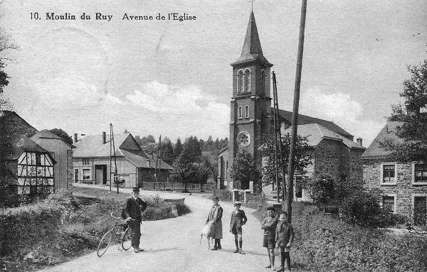 Carte postale : 1910 : l'église Saint-Eustache et à  droite une partie de la ferme Petitjean. Joseph Halconruy (le facteur), Ernestine Gabriel, Cyrille Gabriel, Joseph Mathieu, Roger Gilles